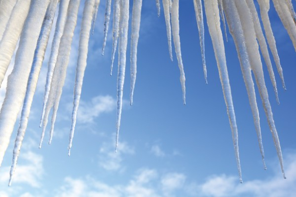 Icicles hanging against a blue sky
